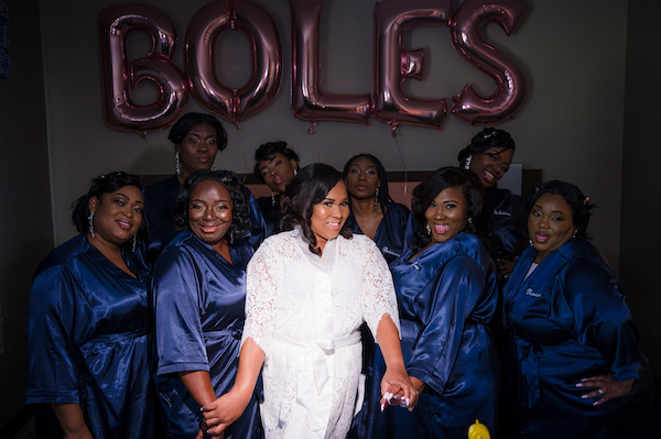 bride in a white robe standing with her bridal party dressed in Navy blue robes
