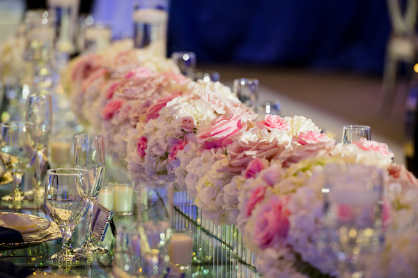 lush pink and white floral pieces on a long mirrored table