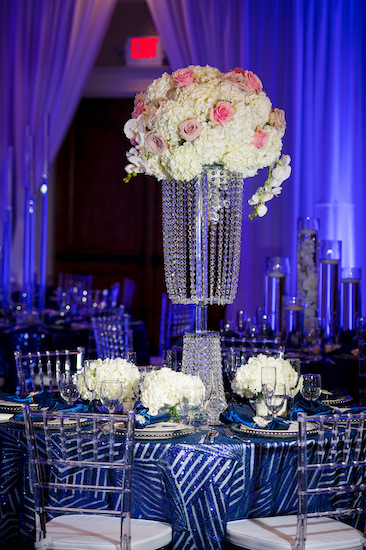 tall crystal centerpieces on a luxurious navy blue and silver tablecloth with acrylic Chiavari chairs