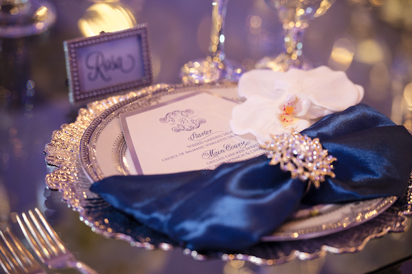silver charger plate with navy blue satin napkins, custom menu card and a rhinestone napkin ring