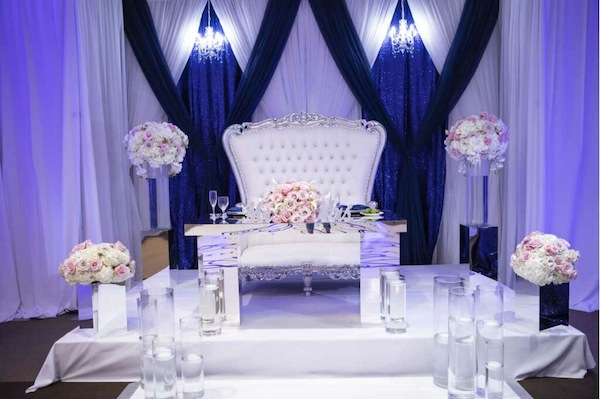 Sophisticated sweetheart table with luxurious blush floral arrangements, floating candles and blue and white draping