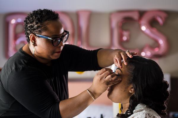 Woman applying eyelashes to a Columbia South Carolina bride on her wedding day
