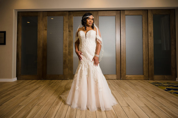 bride wearing an elegant lace and tulle wedding gown with a blush tone