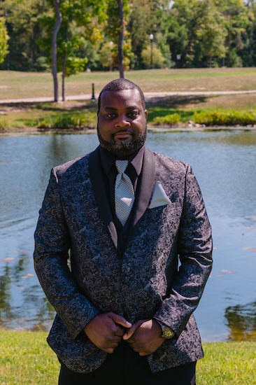 groom standing next to a pond wearing a luxurious patterned tuxedo jacket