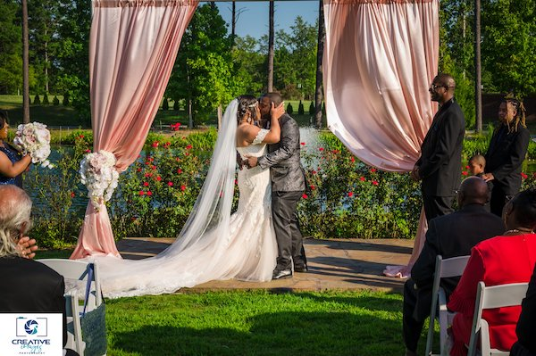 bride and groom kissing under a pink satin draped wedding arch at Doko Manor in Blythewood South Carolina