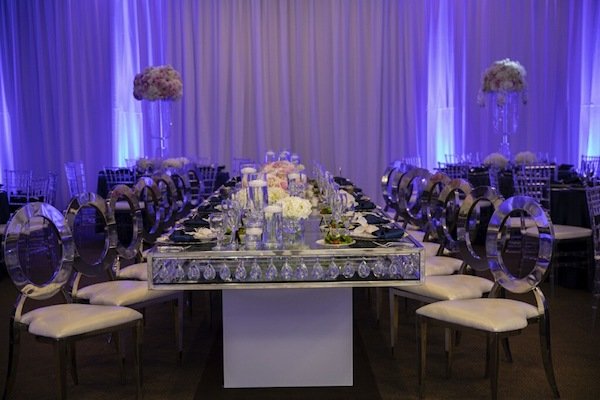 Navy blue, blush and silver wedding decor with long mirrored dining tables and light blue uplighting