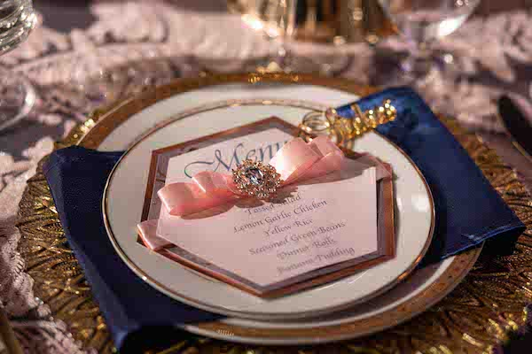 gold place setting with navy blue napkin at a Sophisticated North Charleston