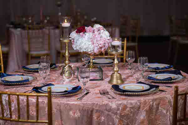 pink and gold wedding reception table with navy blue napkins and custom menu cards