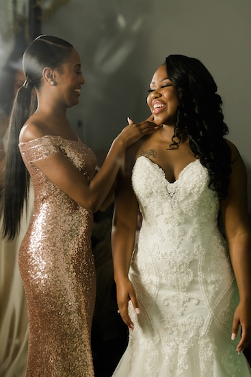 helping the bride finish dressing for her North Charleston wedding ceremony