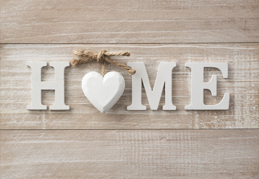A rustic wooden sign reading HOME with a heart in the space of the letter O