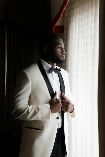 groom in a white tuxedo with black collar posing for a photo at the window