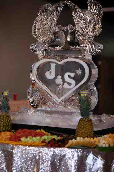 monogrammed ice carving of two doves surrounded by a fruit and cheese display