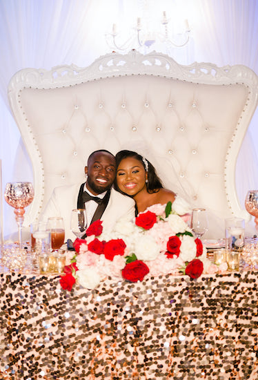 bride and groom sitting at their luxurious sweetheart table