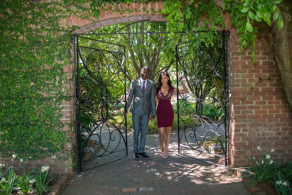 bride and groom to be posing for engagement photos inext to a wrought iron gate