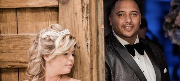 bride and groom on opposite sides of a rustic wooden door