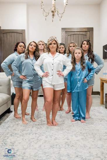 bride and bridal party posing for photos in matching pajamas