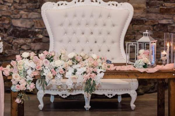 white tufted loveseat behind a rustic farmhouse table with blush and white flowers
