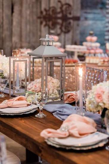 tablescape of blush napkins and flowers with lanterns and dusty blue fabric runner