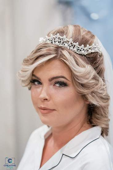 bride getting ready for her wedding day wearing a shimmering tiara