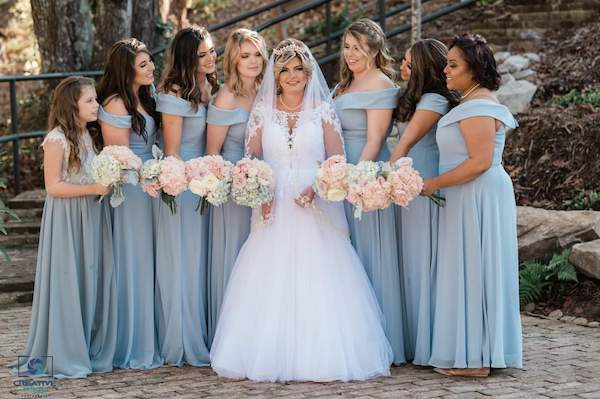 bride and her bridal party wearing dusty blue dresses carrying blush and white flowers