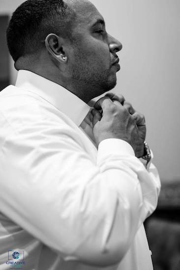 groom buttoning his shirt as he gets dressed for his Catawba Falls Event Center wedding